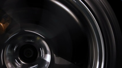 close up shot of a black rims street car tire speeding