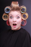 Funny surprised blond girl hair curlers rollers by hairdresser