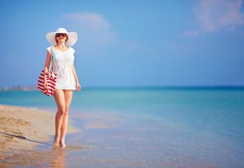 beautiful woman walking the summer beach