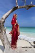 A woman wearing a saree stands on a washed up tree.