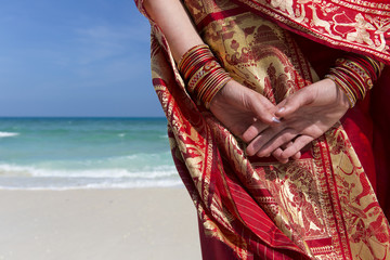 Close up of hands and bangles of a woman on the beach.