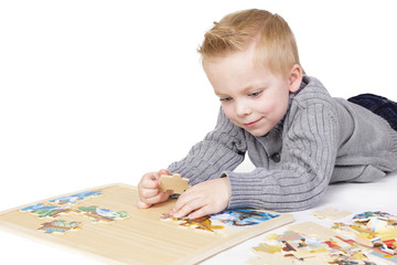 Young boy solving a puzzle. Isolated on white