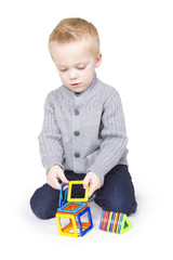 Cute Boy playing with blocks and shapes
