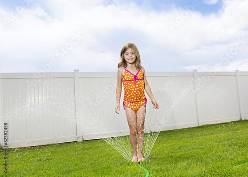 Child playing in the backyard sprinklers
