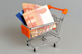 Money, credit card in shopping cart on gray