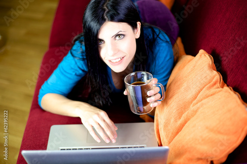 Beautiful woman laying on couch drinking coffee commerce