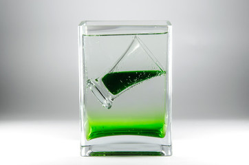 Glass of absinthe in a vase on gray