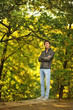 against the backdrop of autumn trees man in jacket and jeans for