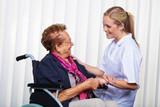 Krankenpflegerin und alte Frau im Rollstuhl