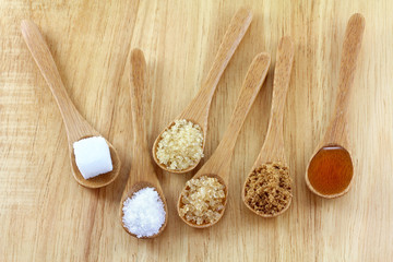 Spoons of different type of sugar on the wooden background