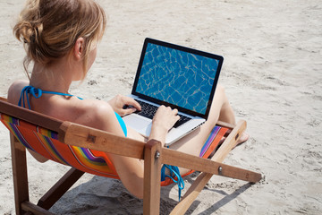 woman working on laptop on the beach
