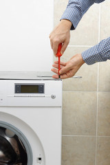 Technician servicing washing machine using screwdriver