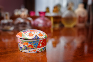Ceramic jewelry box with some perfume in the background