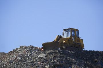 Discarica di rifiuti inerti all'aperto con escavatore