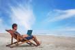 Leinwanddruck Bild - businessman working with computer on the beach