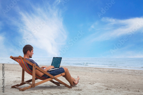 Leinwanddruck Bild businessman working with computer on the beach