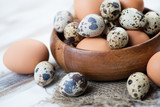 Wooden bowl with raw chicken and quail eggs, close-up
