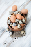 Above view of a wooden bowl with quail and chicken eggs