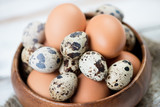 Close-up of chicken and quail eggs in a wooden bowl, studio shot