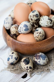 Close-up of raw chicken and quail eggs, vertical shot