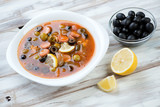 Solyanka: traditional russian soup with meat, sausage and olives