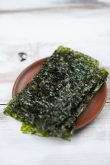 Ceramic saucer with sheets of nori, shallow depth of field