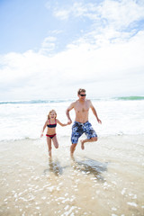 Happy father and daughter running from waves at beach