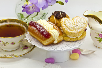Traditional afternoon tea with cream cakes and vintage tea set.