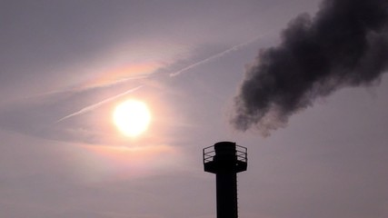 Smokestack against the sky and the sun