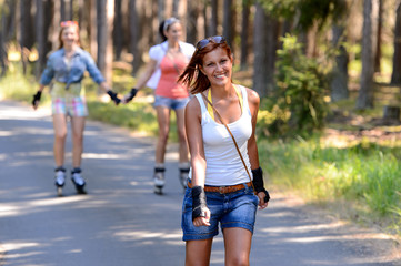 Young woman roller skating outdoors with friends
