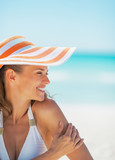 Portrait of smiling woman in hat on beach looking on copy space