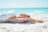 Relaxed young woman tanning on beach