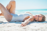 Relaxed young woman laying on beach