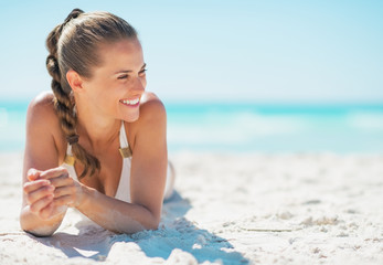Happy young woman laying on beach and looking on copy space