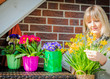 Frau mit Frühlingsblumen auf dem Balkon