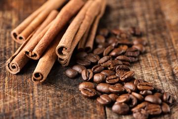 Coffee and cinnamon sticks on grunge wooden background macro