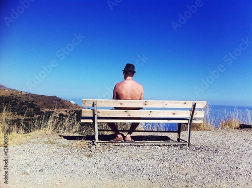 lonely man sitting on the bench looking at the sea