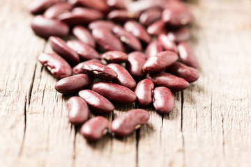 Red beans on wooden background close up