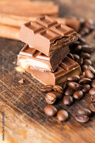 Chocolate candy bar and cofee beans on wooden table closeup