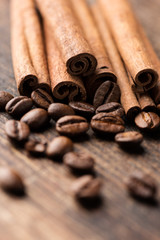 Coffee and cinnamon sticks on wooden background close up vertica
