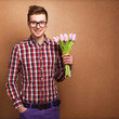 A young romantic man holding a bouquet of flowers isolated