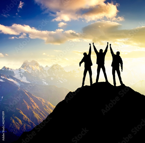 Silhouette of team on mountain peak. Active life concept