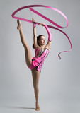 beautiful Caucasian girl gymnast with a ribbon