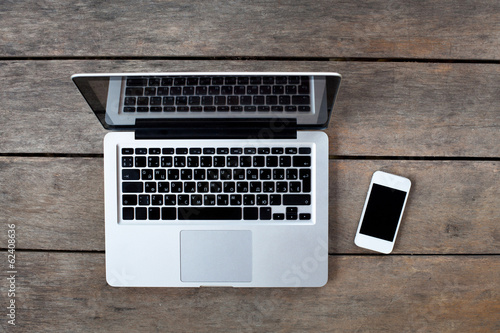 laptop and white smartphone on old wooden desk