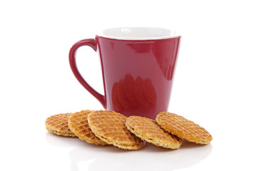 Pile of typical Dutch stroopwafels ( with syrup) near coffee cup