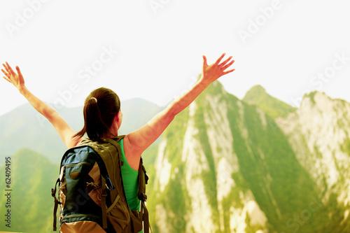 woman hiker stand at peak of mountain huashan checking the map