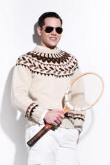 Smiling retro tennis fashion man with sunglasses holding a vinta