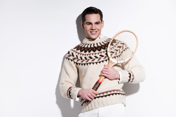 Smiling retro tennis fashion man holding a vintage wooden racket
