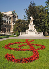 Statue of Amadeus Mozart with flower beds as treble clef in Burg
