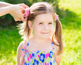 Sweet smiling little girl with her mom's hands making hairstyle